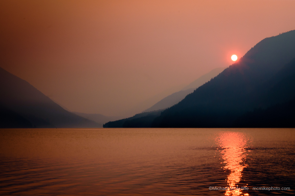 A smoky orange sunset over Lake Crescent in Olympic National Park.